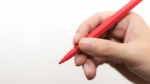 赤ペンを持つ手