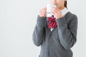 コップを手に持つ女子高生