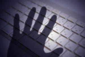 キーボードに伸びる手の影